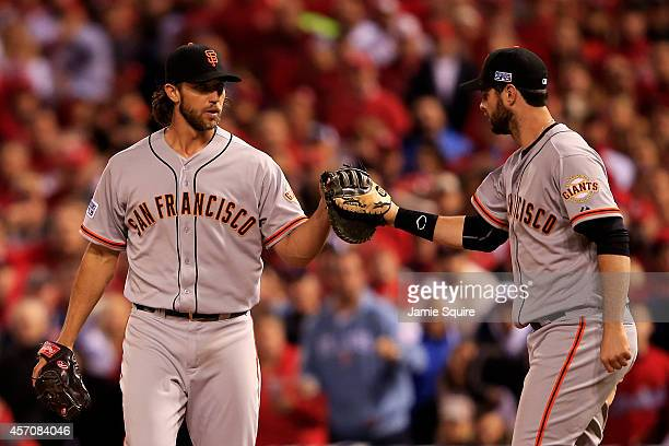 Madison Bumgarner celebrates with Brandon Belt of the San Francisco Giants after tagging out Kolten Wong of the St. Louis Cardinals in the seventh...