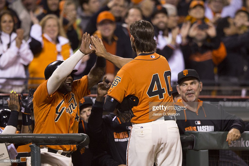 Madison Bumgarner #40 of the San Francisco Giants is congratulated by teammates in the dugout after hitting a grand slam home run against the Colorado Rockies during the fourth inning at AT&T Park on April 11, 2014 in San Francisco, California.