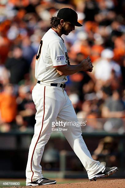 Madison Bumgarner of the San Francisco Giants reacts after his throwing error in the seventh inning against the Washington Nationals during Game...