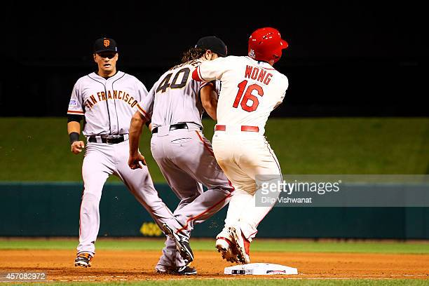 Madison Bumgarner of the San Francisco Giants tags Kolten Wong of the St. Louis Cardinals out in the seventh inning during Game One of the National...