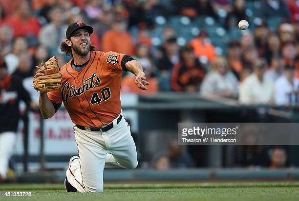 Madison Bumgarner of the San Francisco Giants throws from his knees to first base but not in time to get Todd Frazier of the Cincinnati Reds in the...