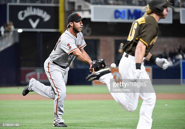 Madison Bumgarner of the San Francisco Giants tosses the ball to first base to get the out on Travis Jankowski of the San Diego Padres during the...