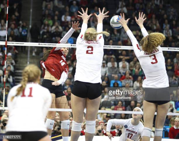 Madison Duello of the Wisconsin Badgers attempts an attack while being dual blocked by Kathryn Plummer and Holly Campbell of the Stanford Cardinal...