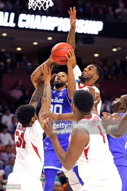 Madison Jones of the Seton Hall Pirates is fouled by Anton Beard of the Arkansas Razorbacks as Arlando Cook goes for the block from behind in the...