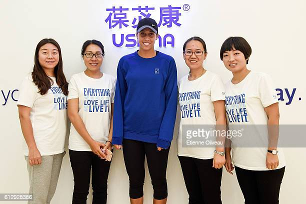 Madison Keys of the United States poses with staff members at the USANA booth on day six of the 2016 China Open at the China National Tennis Centre...