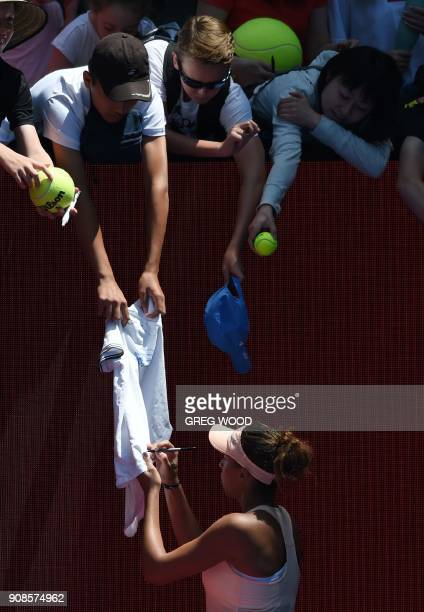 Madison Keys of the US signs a fan's tshirt after beating France's Caroline Garcia in their women's singles fourth round match on day eight of the...