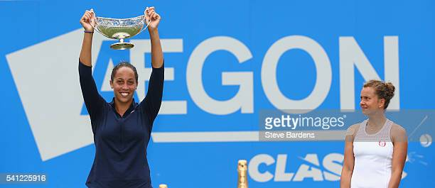 Madison Keys of United States lifts the Maud Watson trophy as Barbara Strycova of Czech Republic looks on after the Women's Singles Final on day...