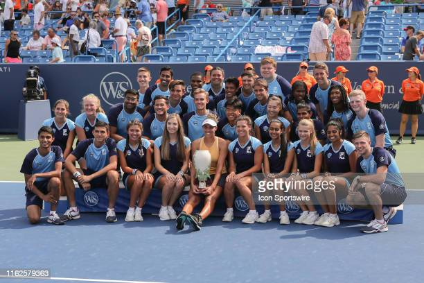 Madison Keys of United States poses with the Rookwood Cup trophy and volunteers after winning the Western Southern Open at Lindner Family Tennis...