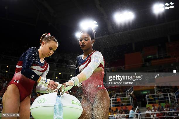 Madison Kocian and Gabrielle Douglas of the United States apply chalk in preparation for competing on the uneven bars during the Artistic Gymnastics...