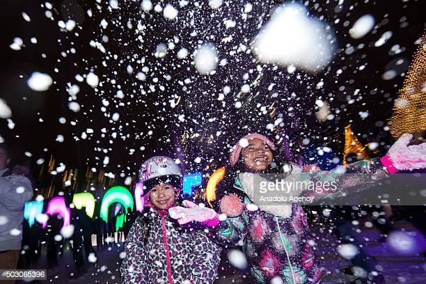 Madison Luces left and Zairah Diamzon throw snow on the ice rink as they await the countdown to midnight at Toronto's Nathan Phillips Square on...