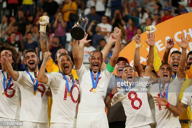 Madjer of Portugal lifts the FIFA Beach Soccer World Cup trophy following his team's victory in the final match against Italy at Estadio Mundialista...