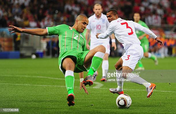 Madjid Bougherra of Algeria tackles Ashley Cole of England during the 2010 FIFA World Cup South Africa Group C match between England and Algeria at...
