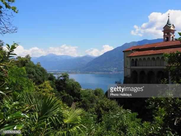 Madonna del Sasso church and green plants above Locarno swiss city, alpine Maggiore lake at...