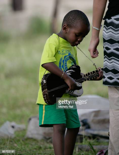 Madonna's adopted son David Banda plays with a guitar as he visits a project previously set up by Madonna's Raising Malawi Foundation at the Namitete...