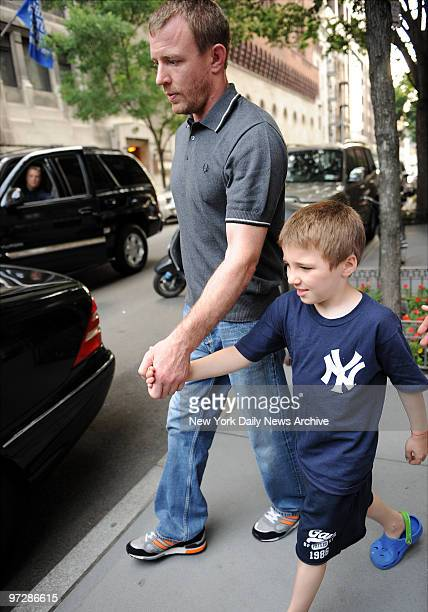 Madonna's husband Guy Ritchie with their son Rocco who is wearing a Yankee jersey with rumors that Madonna is seeing New York Yankee Alex Rodriguez