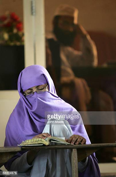 A madrassa student with her head covered in Islamic tradition studies the Quoran as the school principal looks on during class August 4 2005 in...