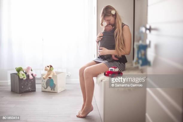 Madre con bambino in fascia. Vita domestica.