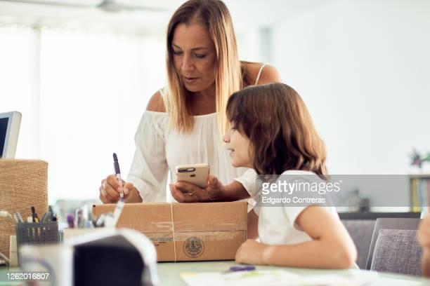 madre e hija empacando un regalo en una caja de cartón - caja de regalo stock pictures, royalty-free photos & images