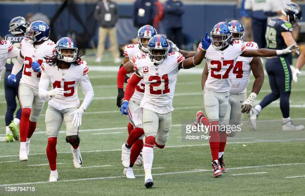Madre Harper, Jabrill Peppers and Isaac Yiadom of the New York Giants celebrate an interception by Darnay Holmes against the Seattle Seahawks during...