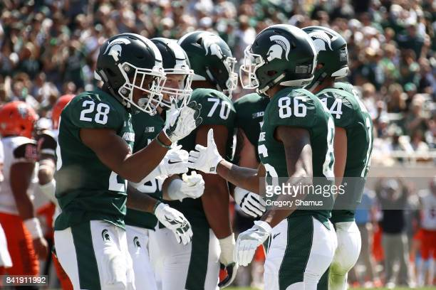 Madre London of the Michigan State Spartans celebrates a first half touchdown with Trishton Jackson while playing the Bowling Green Falcons at...