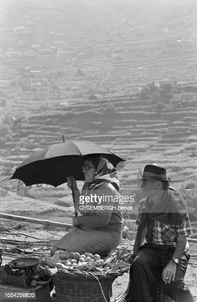Madère Portugal septembre 1978 Un couple de paysans madérois vendant des fruits dans la montagne La femme s'abrite du soleil à l'aide d'un parapluie...