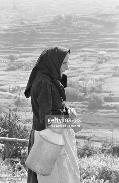 Madère Portugal septembre 1978 Vieille femme madéroise coiffée d'un voile noir marche dans la montagne en portant un pot à lait