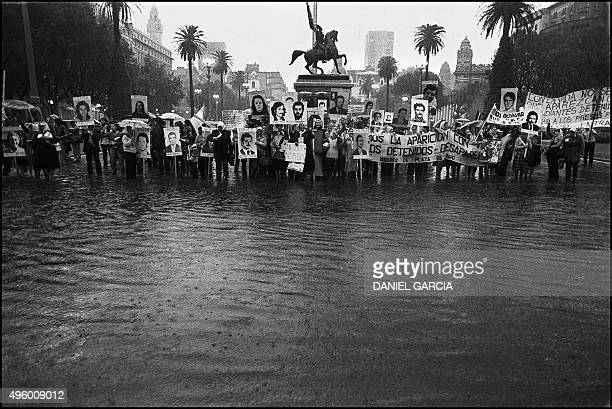 Madres de Plaza de Mayo remain upright on the flooding square in front of the Presidential Palace claiming for their missing sons and daughters circa...