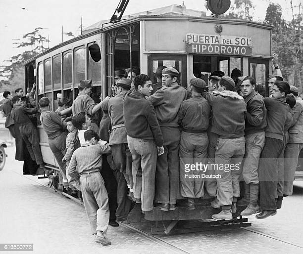 Madrid commercial life is now coming back almost to normal Rush hour crowds pour from office and factory and crowd on to the few tram cars which...