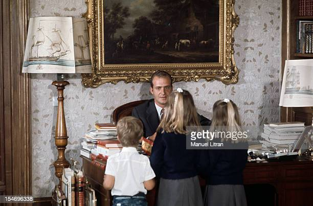 Madrid July 1971 at the Zarzuela Palace the three children of Prince Juan Carlos of Spain here sitting behind his desk stand back facing their father...