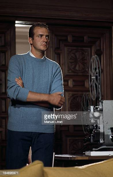 Madrid July 1971 Juan Carlos of Spain at his home in his palace of the Zarzuela standing dressed in a sweater with sleeves rolled up watch a movie...