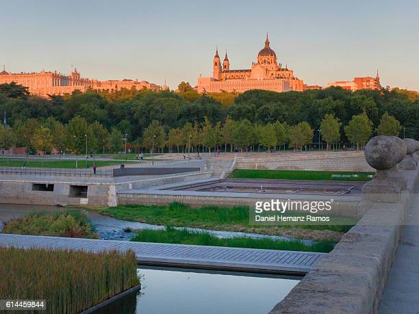 Madrid park with Manzanares river in foreground and the cathedral of Madrid and Royal Palace in Background. Madrid Rio park. Madrid