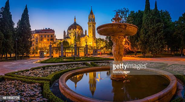 Madrid Retiro Park fountains ornate church towers illuminated dusk Spain