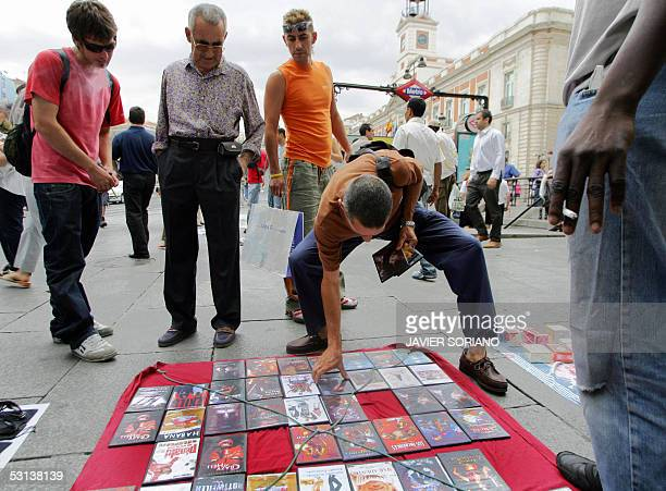 People look at pirated DVDs exhibited at Sol square in Madrid 23 June 2005 The International Federation of Phonographic Industries IFPI in the annual...