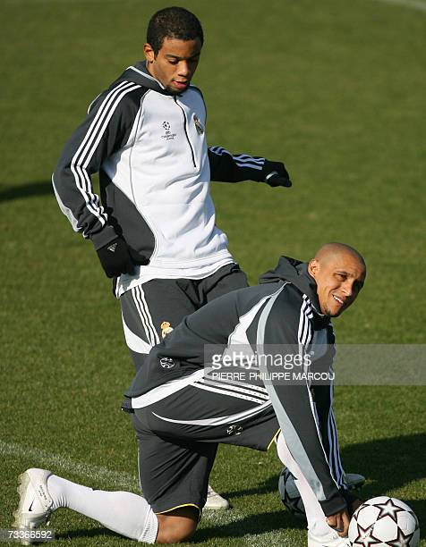 Real Madrid's Brazilian defender Marcelo Vieira jokes with teammate Roberto Carlos during a training session in Madrid 19 February 2007 on the eve of...