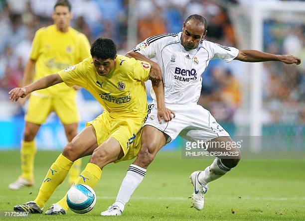 Real Madrid's Emerson fights for the ball with Villarreal's Argentina Juan Riquelme during their Spanish league football match at the Santiago...