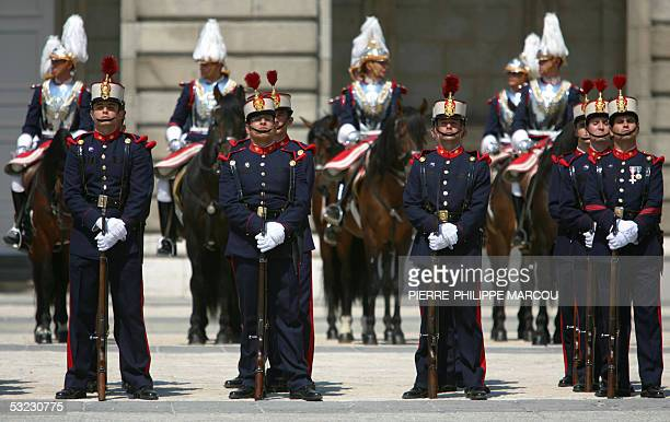 Spanish royal guards listen to the British anthem in memory of the victims of the 07 July London bombing during a change of guards 13 July 2005 at...