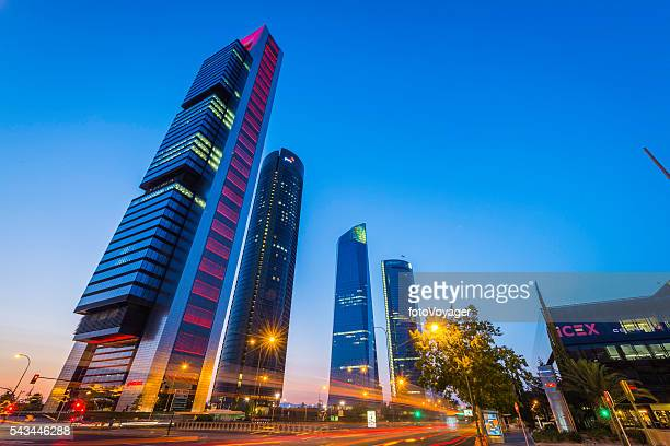 Madrid traffic zooming past Cuatro Torres illuminated at sunset Spain