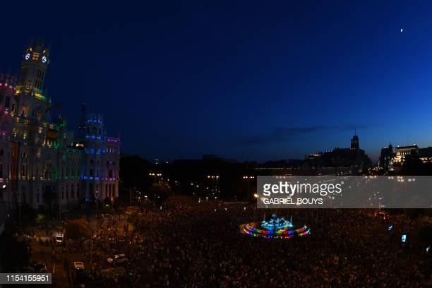 TOPSHOT Madrid´s City hall and the Cibeles fountain are illuminated with the colors of the rainbow flag during the annual Pride parade in Madrid on...