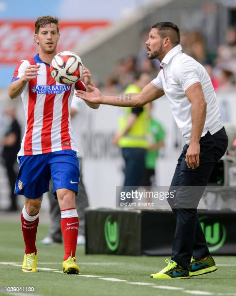 Madrid's head coach Diego talks to his player Cristian Ansaldi during the soccer test match between VfL Wolfsburg and Atletico Madrid at Volkswagen...