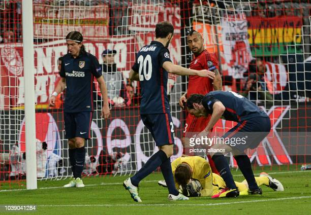 Madrid's Jan Oblak makes a save shortly before the final whistle with teammates Filipe Luis Juanfran Torres Munich's Arturo Vidal and Madrid's Diego...