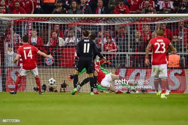 Madrid's Portuguese forward Cristiano Ronaldo shoots the first goal during the UEFA Champions League 1st leg quarterfinal football match FC Bayern...