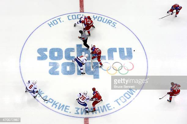 Mads Hansen of Norway faces off with Pavel Datsyuk of Russia to start the Men's Ice Hockey Qualification Playoff game on day eleven of the Sochi 2014...