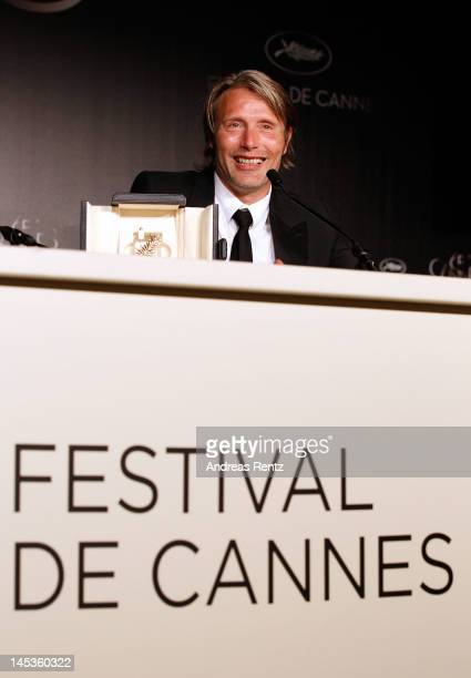 Mads Mikkelsen with his Best Actor Award for his role in 'The Hunt' smiles as he attends the Winners Press Conference during the 65th Annual Cannes...