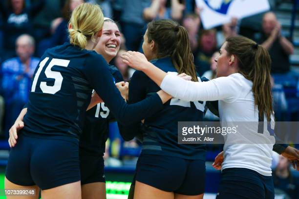 Mady Arles of Emory University centerleft celebrates a point scored with teammates during the Division III Women's Volleyball Championship held at...