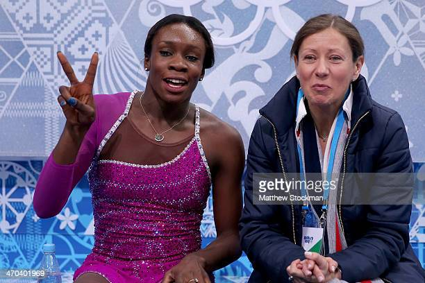 Mae Berenice Meite of France waits for her score with her coach Katia Krier Beyer in the Figure Skating Ladies' Short Program on day 12 of the Sochi...