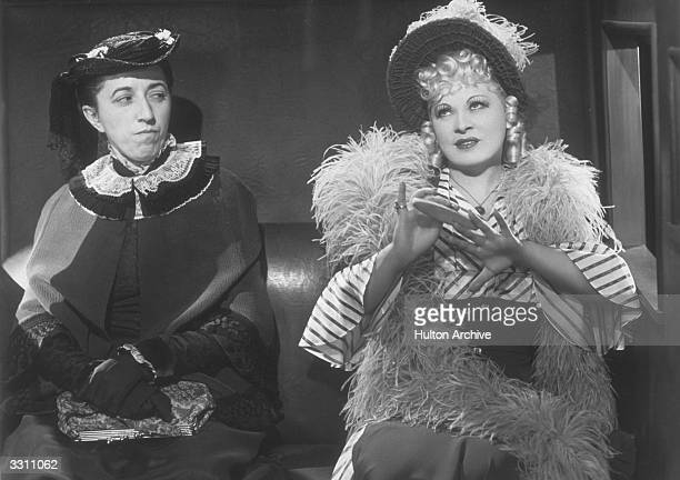Mae West files her nails in a train carriage under the disapproving eye of Margaret Hamilton in a scene from the film 'My Little Chickadee' directed...