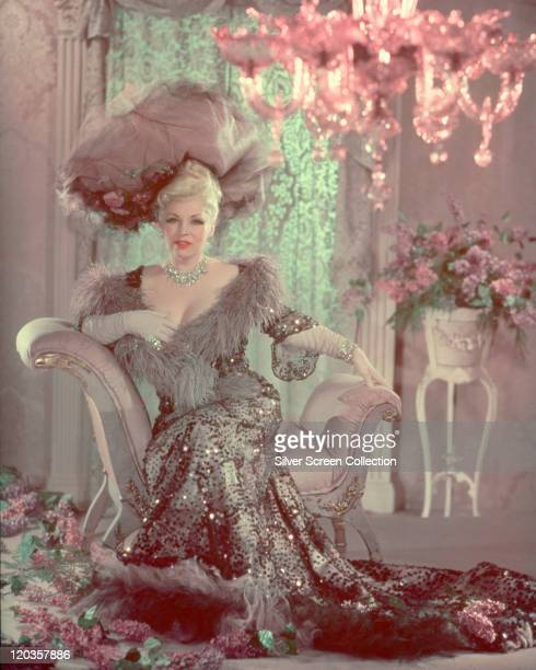 Mae West , US actress, in period costume , sitting on a backless armchair in a studio portrait, with pink flowers in the background and strewn across...