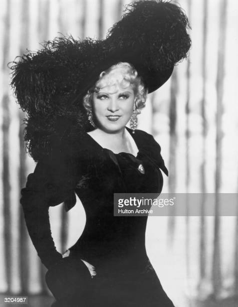 Mae West wears a period costume, including a large hat with trimmed with ostrich feathers, in a promotional portrait for director A. Edward...