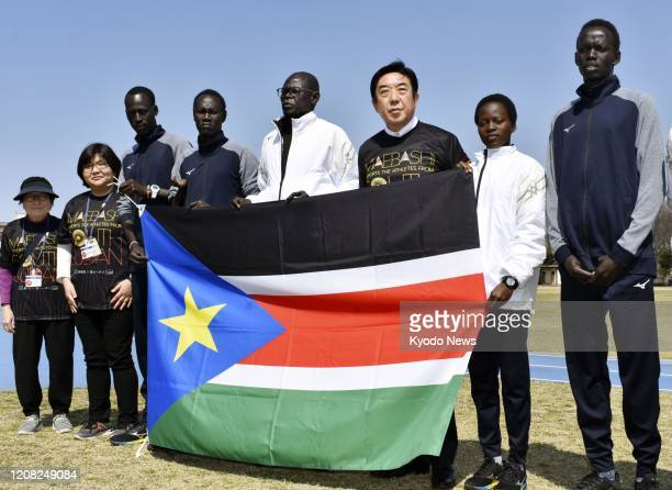 Maebashi Mayor Ryu Yamamoto and five South Sudanese athletes pose for a photo on March 26 with the country's national flag in the eastern Japan city...