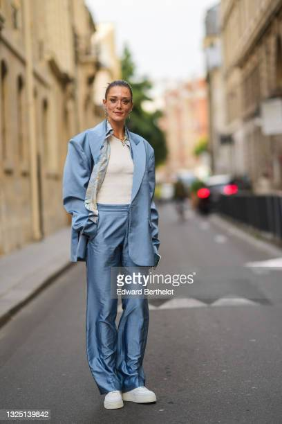 Maeva Giani Marshall wears long earrings, a shirt with printed patterns, a white t-shirt, a blue oversized silky / lustrous blazer jacket, matching...